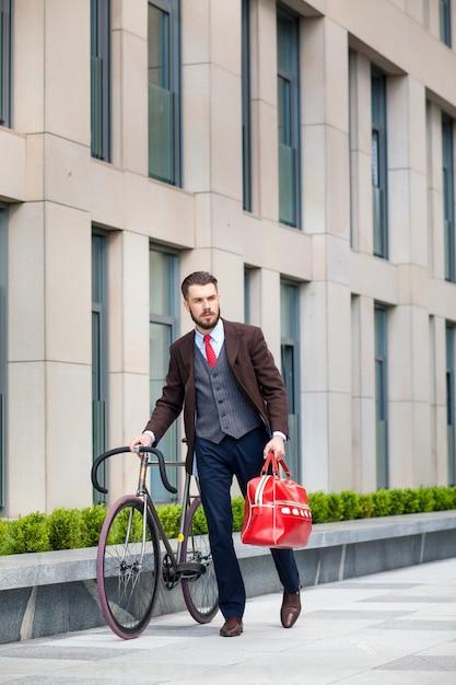 Hübscher geschäftsmann in einer jacke und einer roten tasche und seinem fahrrad auf den straßen der stadt. Kostenlose Fotos