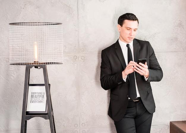 Hübscher geschäftsmann mit dem smartphone, der auf wand sich lehnt Kostenlose Fotos