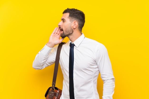 Hübscher geschäftsmann über lokalisierter gelber wand, die mit dem breiten mund schreit, öffnen sich Premium Fotos