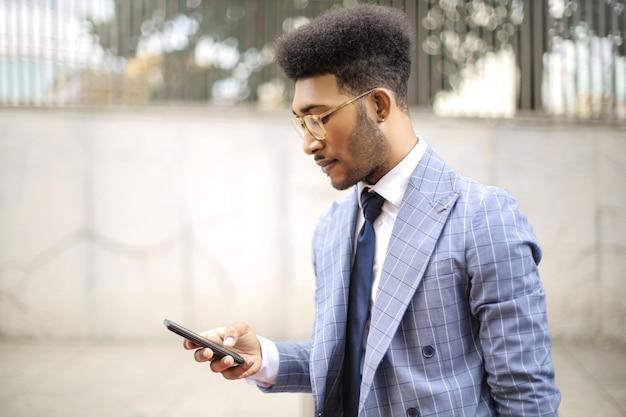 Hübscher geschäftsmann unter verwendung der kopfhörer, zum mit seinem telefon zu nennen Premium Fotos