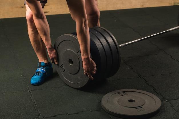 Hübscher gewichtheber, der sich auf das training mit der langhantel vorbereitet Premium Fotos