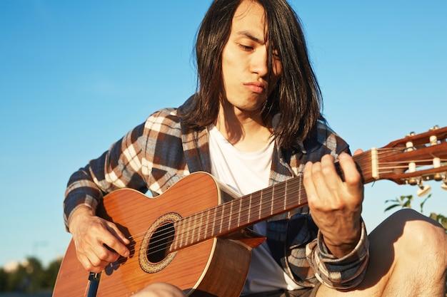 Hübscher gitarrist, der draußen übt Kostenlose Fotos
