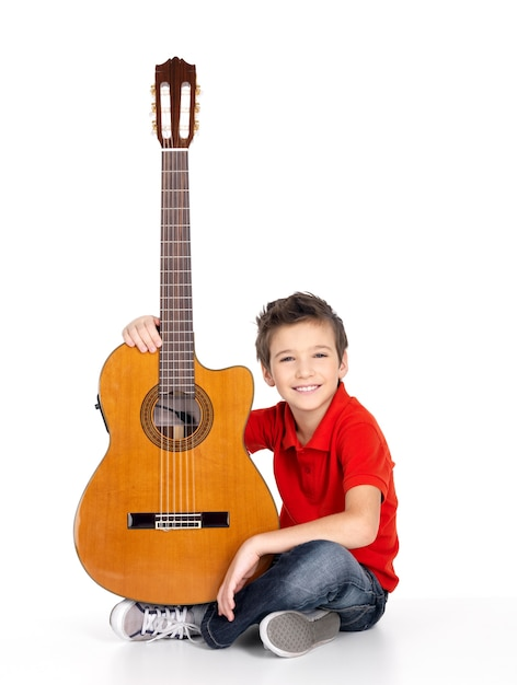 Hübscher glücklicher junge mit der akustikgitarre lokalisiert auf weißem hintergrund Kostenlose Fotos