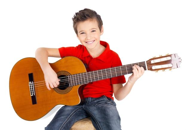 Hübscher glücklicher junge spielt auf der auf weiß isolierten akustikgitarre Kostenlose Fotos