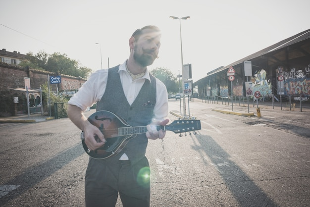Hübscher großer schnurrbarthippie-mann, der mandoline spielt Premium Fotos