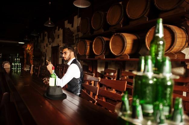 Hübscher gut gekleideter arabischer mann mit glas whisky und zigarre warf an der kneipe auf. Premium Fotos