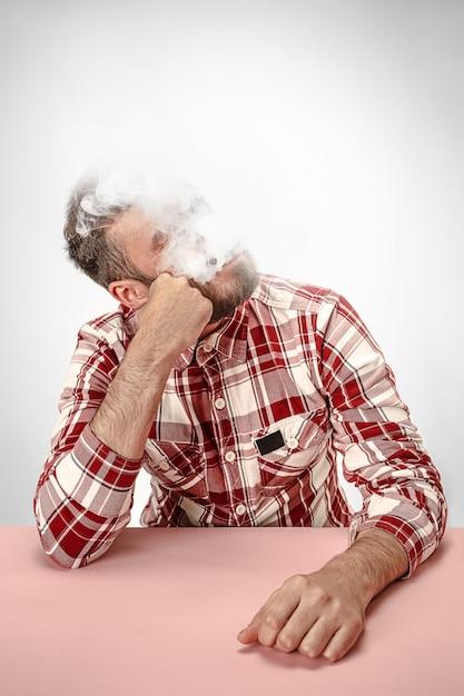 Hübscher hipstermann, der zigarette zu hause raucht Kostenlose Fotos