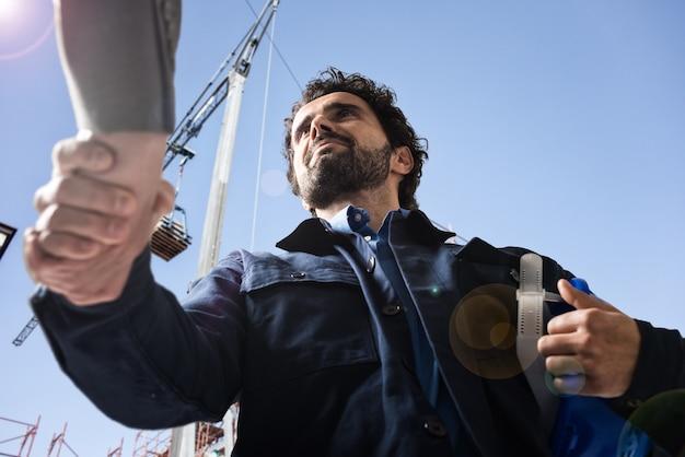 Hübscher ingenieur, der einen händedruck in einer baustelle gibt Premium Fotos