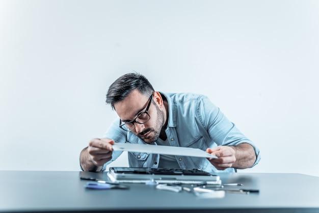 Hübscher ingenieur, der reparierte laptop-computer zusammenbaut. Premium Fotos