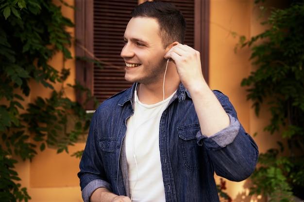 Hübscher junge in einem jeanshemd hört musik in den kopfhörern draußen Kostenlose Fotos