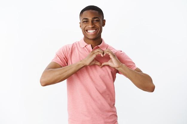 Hübscher junger afroamerikaner mit rosa polo-t-shirt Kostenlose Fotos