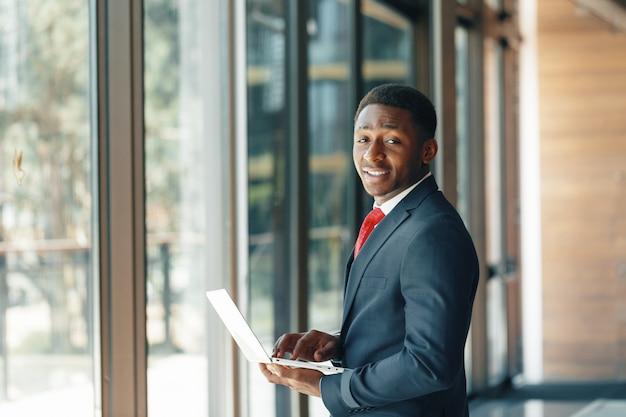 Hübscher junger afroamerikanischer geschäftsmann in der klassischen klage, die einen laptop und ein lächeln hält Premium Fotos