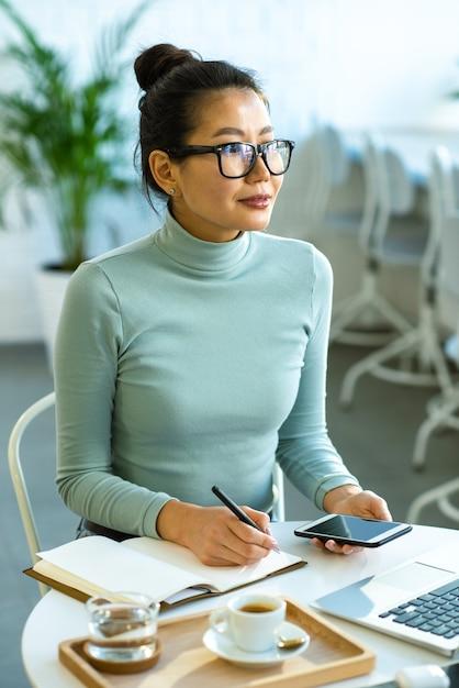 Hübscher junger asiatischer student in brille und blauem pullover, der inspiriert wird, während er über these durch tasse tee im college-café arbeitet Premium Fotos