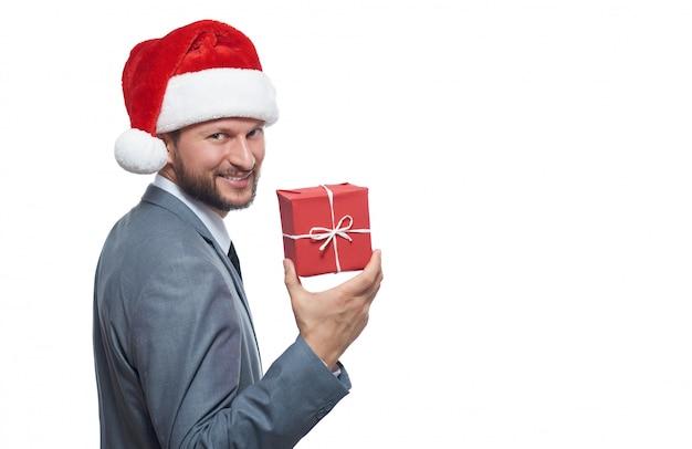 Hübscher junger bärtiger geschäftsmann in einer weihnachtsmütze, die ein kleines weihnachtsgeschenk zeigt, das freudig lächelt Kostenlose Fotos