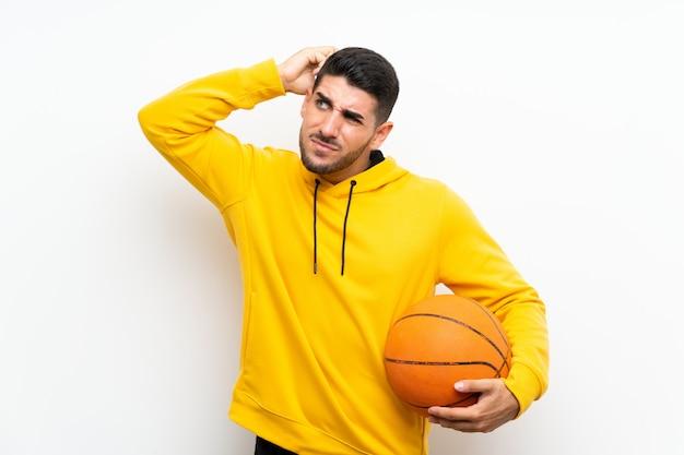 Hübscher junger basketball-spielermann über der lokalisierten weißen wand, die zweifel und mit hat, verwirren gesichtsausdruck Premium Fotos