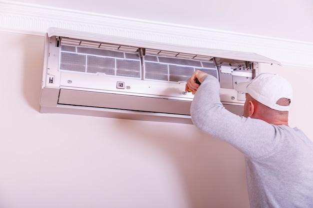 Hübscher junger elektriker, der klimaanlage in einem kundenhaus installiert. reinigung der klimaanlage. mann in handschuhen überprüft den filter. Premium Fotos