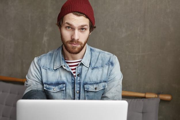Hübscher junger freiberufler mit bart, der jeansjacke und kastanienbraunen hut trägt, der am kaffeehaus sitzt Kostenlose Fotos