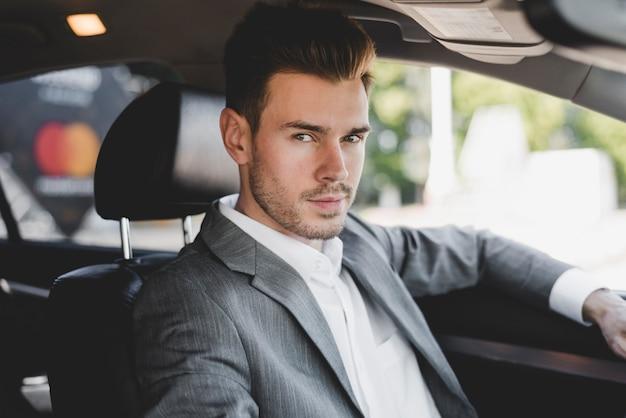 Hübscher junger geschäftsmann im auto Kostenlose Fotos