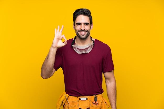 Hübscher junger handwerker, der okayzeichen mit den fingern zeigt Premium Fotos