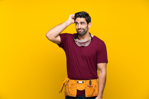 Hübscher junger handwerker über dem lokalisierten gelb, das zweifel hat und mit verwirren gesichtsausdruck Premium Fotos