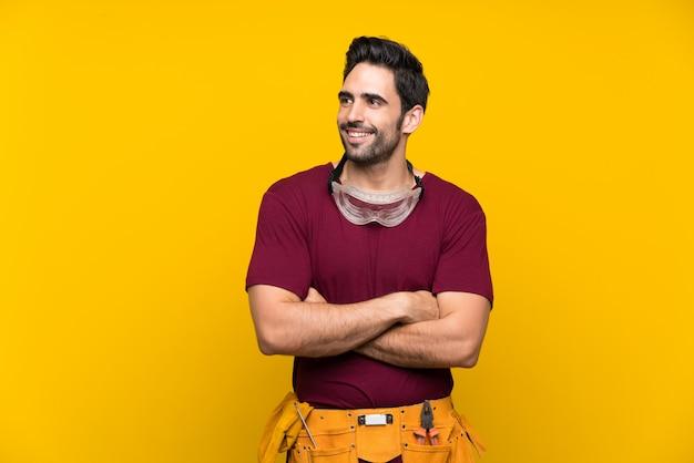 Hübscher junger handwerker über dem lokalisierten gelben hintergrund, der oben beim lächeln schaut Premium Fotos