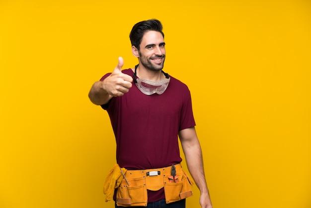 Hübscher junger handwerker über lokalisiertem gelb mit den daumen oben, weil etwas gutes geschehen ist Premium Fotos