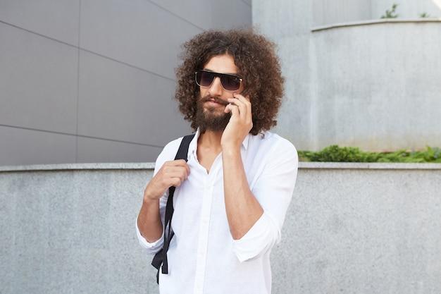 Hübscher junger lockiger mann mit bart, der an sonnigem tag die straße entlang geht, während er am telefon spricht, weißes hemd und schwarzen rucksack tragend Kostenlose Fotos