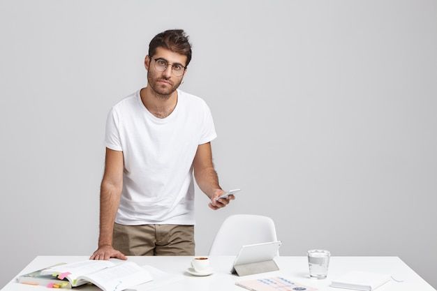 Hübscher junger männlicher wirtschaftslehrer mit stoppeln, die am weißen schreibtisch mit lehrbüchern stehen Kostenlose Fotos