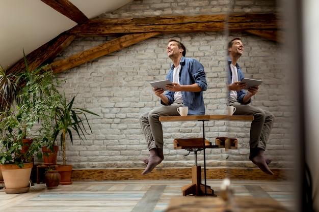 Hübscher junger mann, der digitale tablette beim sitzen im rustikalen raum verwendet Premium Fotos