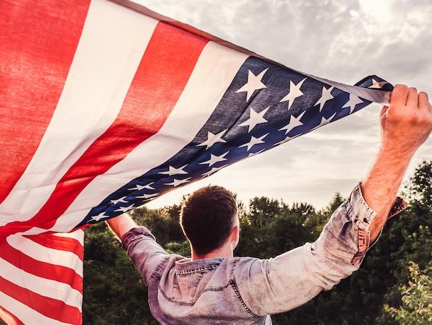 Hübscher, junger mann, der eine amerikanische flagge hält Premium Fotos