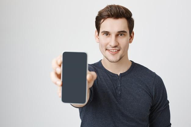 Hübscher junger mann, der handyanzeige zeigt Kostenlose Fotos