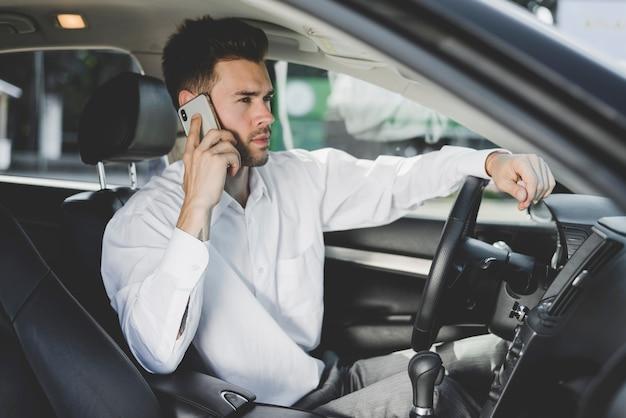 Hübscher junger mann, der im auto spricht am handy sitzt Kostenlose Fotos