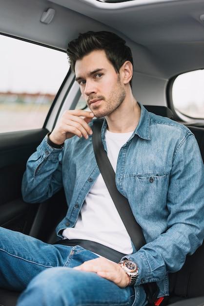Hübscher junger mann, der im autositz betrachtet kamera sitzt Kostenlose Fotos