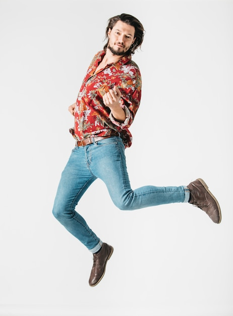 Hübscher junger mann, der in einer luft gegen weißen hintergrund springt Kostenlose Fotos