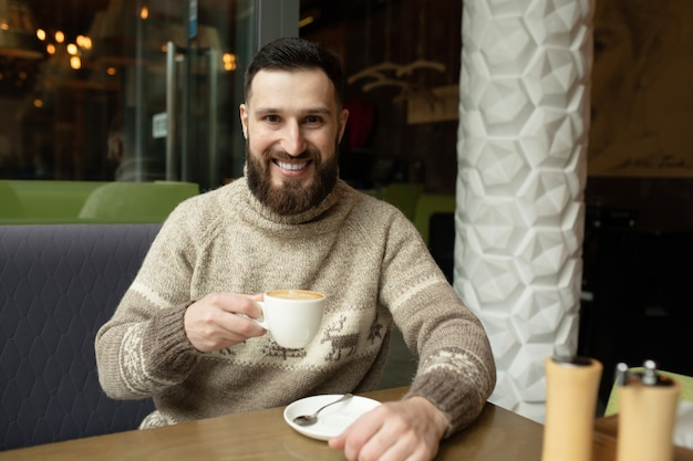 Hübscher junger mann, der kaffee am kaffeehaus trinkt Premium Fotos