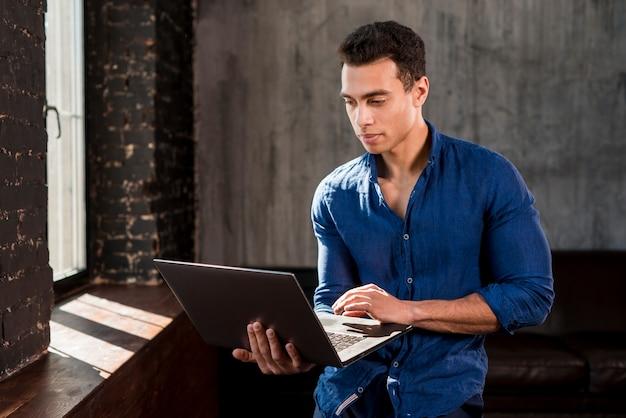 Hübscher junger mann, der laptop nahe dem fenster verwendet Kostenlose Fotos