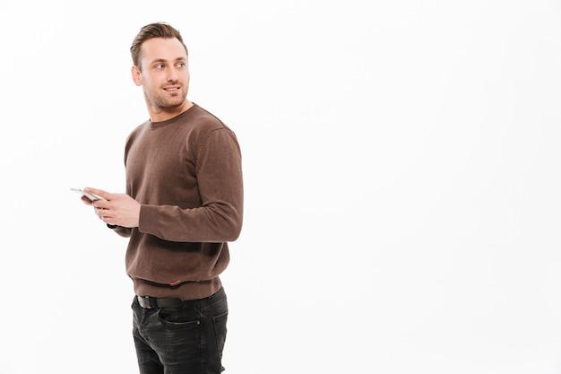 Hübscher junger mann, der mit dem handy plaudert Kostenlose Fotos