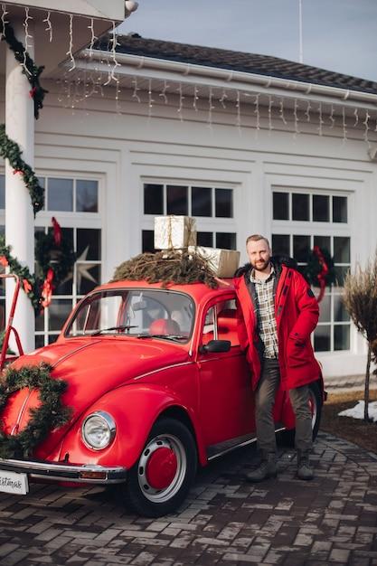 Hübscher junger mann im roten mantel, der durch ein rotes altes auto nahe einem haus steht Kostenlose Fotos