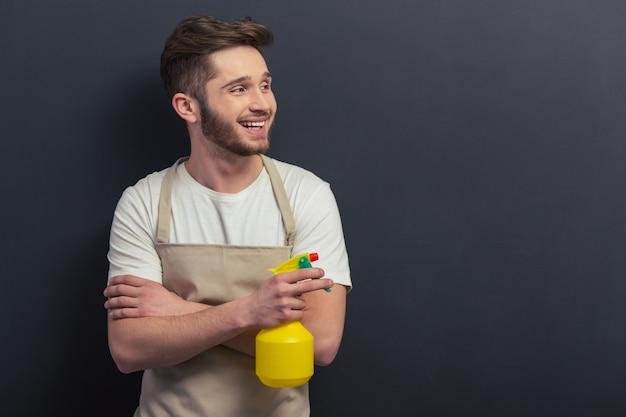 Hübscher junger mann im schutzblech hält einen sprüher. Premium Fotos