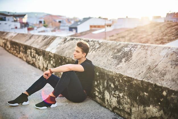Hübscher junger mann im schwarzen, das auf der straße aufwirft Premium Fotos