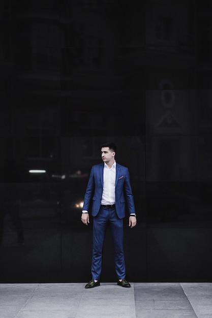 Hübscher junger mann im vollen anzug und in den schuhen, die gegen wand aufwerfen Premium Fotos