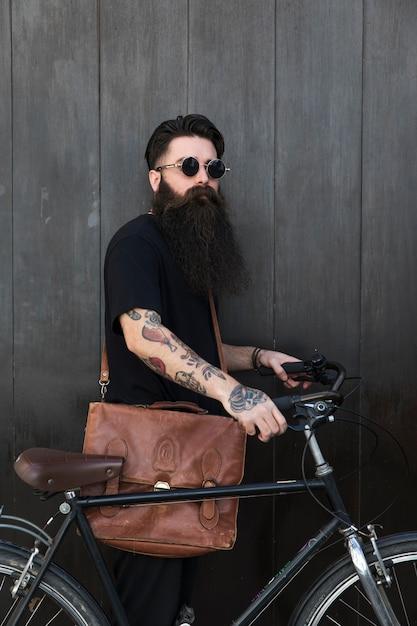 Hübscher junger mann mit dem fahrrad, das vor hölzerner schwarzer wand steht Kostenlose Fotos