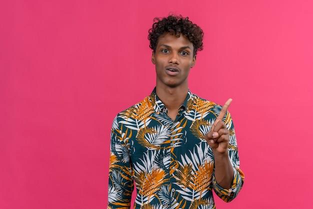 Hübscher junger mann mit dunkler haut zeigt mit dem zeigefinger, der endlich hervorragende ideen bekam, seinen plan zu teilen und albern Kostenlose Fotos
