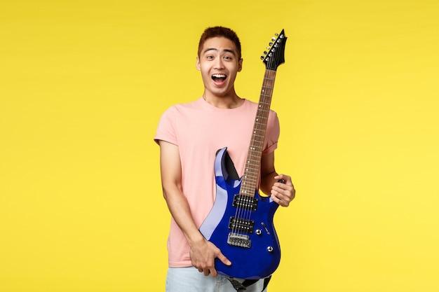Hübscher junger musiker, der die gitarre spielt und, lokalisiert singt Premium Fotos