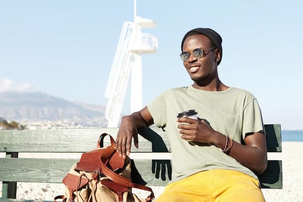Hübscher junger schwarzer europäischer männlicher reisender gekleidet in der trendigen kleidung, die einige minuten ruhe auf bank hat, tee oder kaffee aus pappbecher während des langen spaziergangs durch den ferienort tagsüber trinkt Kostenlose Fotos