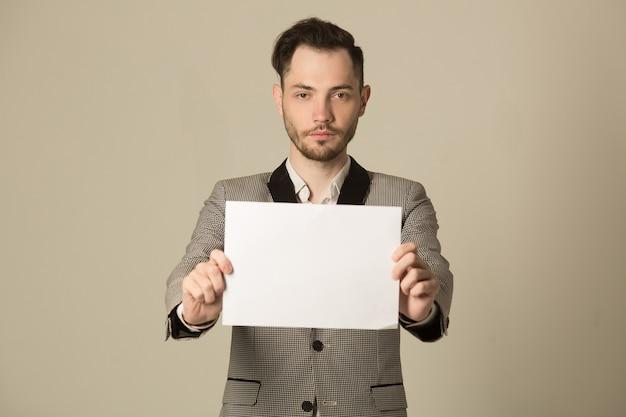 Hübscher junger stilvoller mann in einer jacke, die ein zeichen in seinen händen hält Premium Fotos