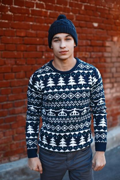 Hübscher junger stilvoller mann in einer vintage-strickmütze in einem gestrickten blauen pullover mit weihnachtsmustern in jeansständern Premium Fotos