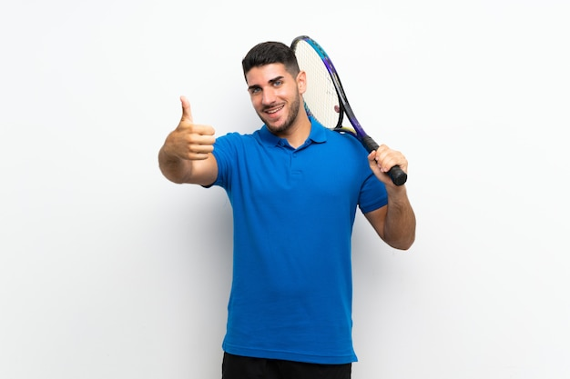 Hübscher junger tennisspielermann auf weißer wand mit den daumen oben, weil etwas gutes geschehen ist Premium Fotos