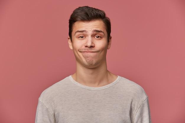 Hübscher junger trauriger kerl mit hochgezogenen augenbrauen trägt in leerem t-shirt, schaut mit misstrauen in die kamera, steht über rosa hintergrund. Kostenlose Fotos