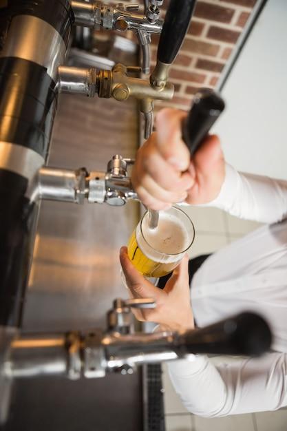 Hübscher kellner, der ein halbes liter bier gießt Premium Fotos